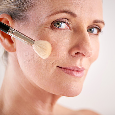 Buy stock photo Closeup studio shot of an attractive mature woman applying makeup with a brush