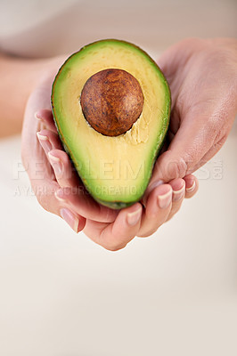 Buy stock photo Cropped shot of a woman holding half an avocado in her cupped hands
