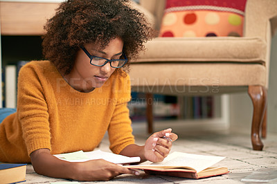 Buy stock photo Cropped shot of a young woman lying on the floor while studying