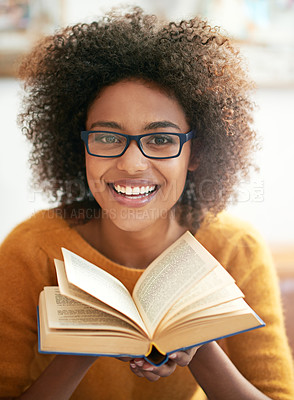 Buy stock photo Cropped portrait of a young woman paging through a book