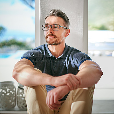 Buy stock photo Shot of a man looking thoughtful while sitting at home