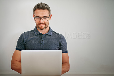 Buy stock photo Shot of a man using his laptop while sitting against a gray wall
