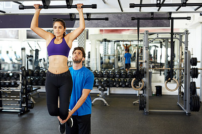 Buy stock photo Cropped shot of a young woman doing pull ups with her personal trainer in the gym