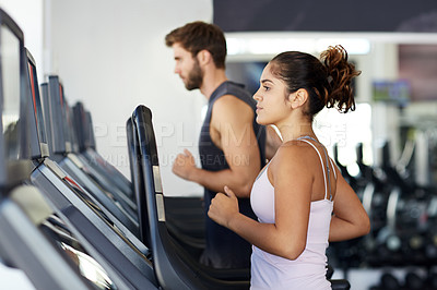 Buy stock photo Cropped shot of two young people running on the treadmills at the gym