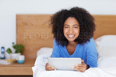 Buy stock photo Shot of a young woman using a digital tablet while lying on her bed