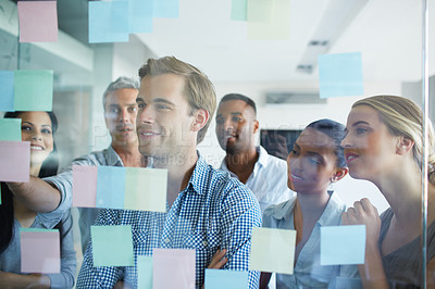 Buy stock photo Shot of a group of colleagues brainstorming together with sticky notes in an office