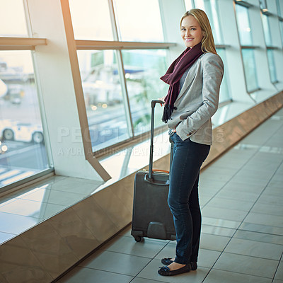Buy stock photo Portrait of a young woman standing with her luggage in an airport
