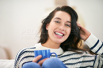 Buy stock photo Shot of a young woman having a cup of coffee while relaxing at home