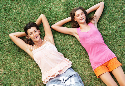 Buy stock photo Top view of mother and daughter relaxing on grass with hands behind head