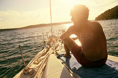 Buy stock photo Shot of a man relaxing on a yacht