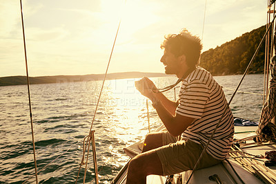 Buy stock photo Shot of a man taking a picture while sitting on a yacht