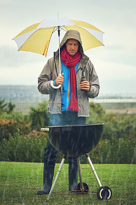 Buy stock photo Shot of a man barbecuing in the rain