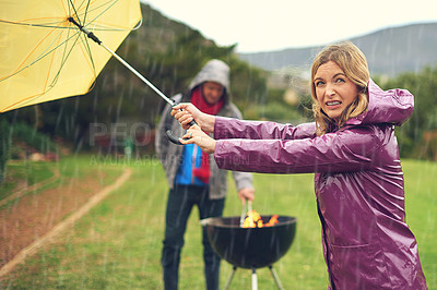 Buy stock photo Shot of a couple trying to barbecue in the rain