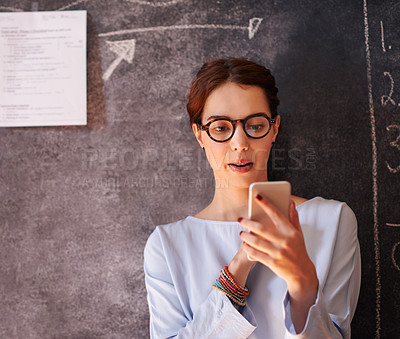 Buy stock photo Cropped shot of a young teacher sending a text while leaning on a chalkboard