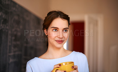 Buy stock photo Cropped shit of a young teacher drinking coffee while standing in front of the chalkboard in her classroom