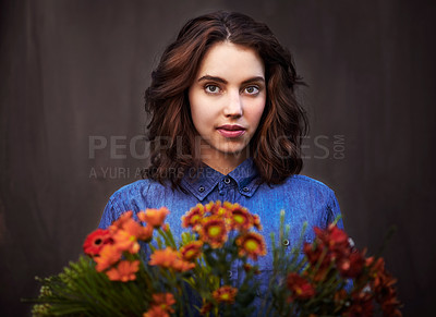 Buy stock photo Portrait of a young woman holding a bouquet of flowers