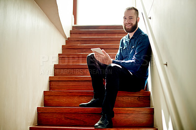 Buy stock photo Full length portrait of a young man using his digital tablet while sitting on a staircase at home