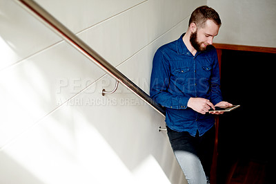 Buy stock photo Cropped shot of a young man using his digital tablet while standing on a staircase at home