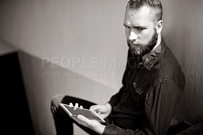 Buy stock photo Cropped shot of a young man using his digital tablet while sitting on a staircase at home in black and white