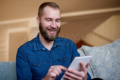 Buy stock photo Cropped shot of a young man using his digital tablet while sitting on a sofa at home
