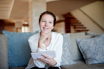 Buy stock photo Cropped shot of a young woman using her tablet while sitting on the sofa at home