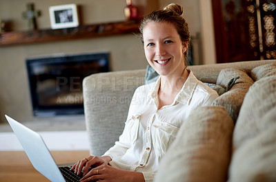 Buy stock photo Shot of a young woman using her laptop while sitting on the sofa at home