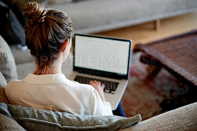 Buy stock photo Rearview shot of a young woman using her laptop while sitting on the sofa at home