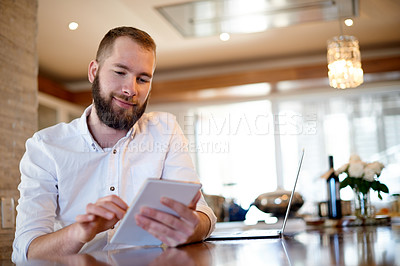 Buy stock photo Shot of a young man using a digital tablet at home