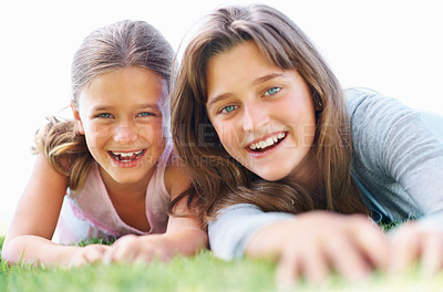 Buy stock photo Closeup portrait of two sisters lying on grass and smiling