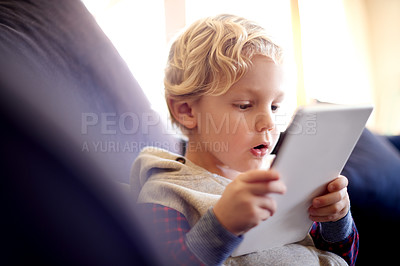 Buy stock photo Cropped shot of a little boy using a digital tablet at home