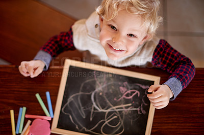 Buy stock photo High angle shot of a little boy drawing on a chalkboard