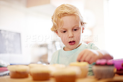 Buy stock photo Shot of a little boy decorating cupcakes in the kitchen