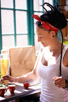 Buy stock photo Shot of a young woman with dreadlocks making coffee at home