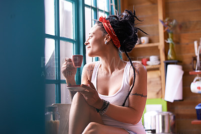 Buy stock photo Shot of an attractive woman with dreadlocks having a cup of coffee in the kitchen
