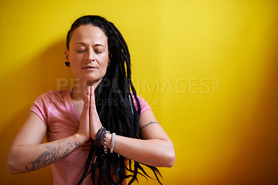 Buy stock photo Shot of a young woman with dreadlocks meditating against a yellow background