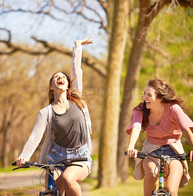 Buy stock photo Shot of two friends out for a bike ride in a park