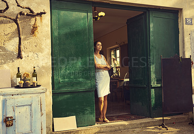 Buy stock photo Shot of a young woman standing in the doorway of a restaurant