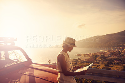 Buy stock photo Shot of a young woman reading a map while out on a road trip