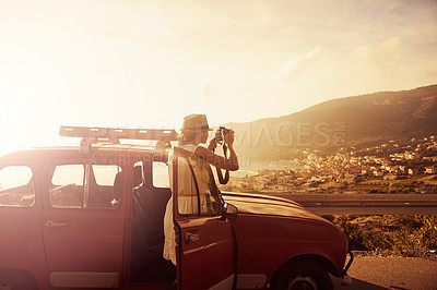 Buy stock photo Shot of a woman taking pictures with her camera while on a roadtrip