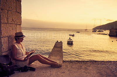 Buy stock photo Shot of a young woman reading a book while out traveling