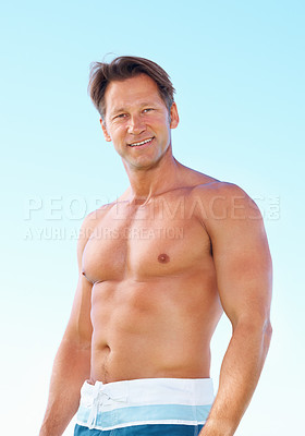 Buy stock photo Portrait of fit muscular man in shorts standing against sky and smiling