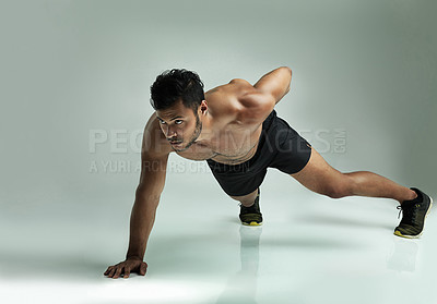 Buy stock photo Studio shot of a young man doing a one hand pushup against a gray background
