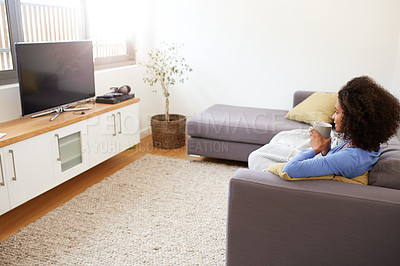 Buy stock photo Shot of a young woman watching television at home