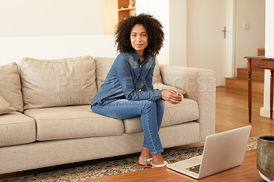 Buy stock photo Shot of a young woman sitting on the sofa at home
