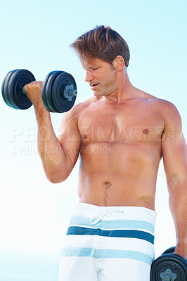 Buy stock photo Fit man in shorts standing against sky lifting dumbbells