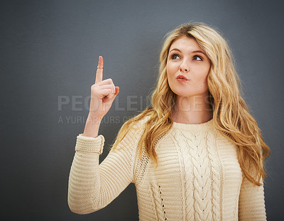 Buy stock photo Shot of a young woman standing against a gray background