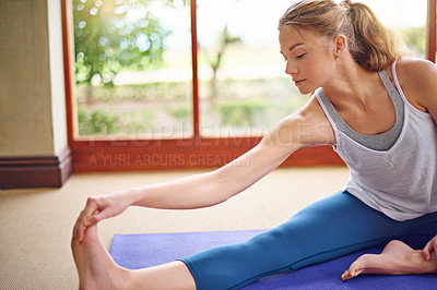 Buy stock photo Shot of a young woman doing yoga at home