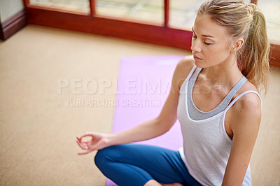 Buy stock photo Shot of a young woman meditating at home