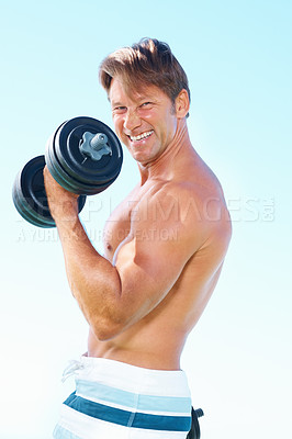 Buy stock photo Portrait of middle aged man in shorts standing against sky lifting dumbbells, smiling back at you