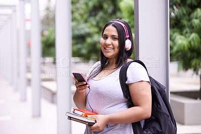 Buy stock photo Portrait of a smiling university student listening to music while standing on campus